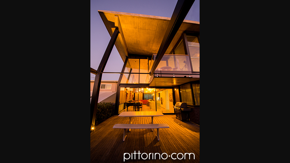 glass fibre reinforced concrete sculpted outdoor dining table and bench seats in the evening, Sydney Eastern Suburbs, Australia